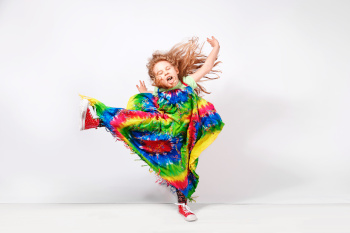 Happy blonde child girl in hippie colorful dress against white wall.