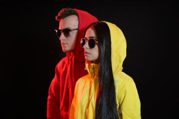 Toned portrait of stylish young couple on dark background